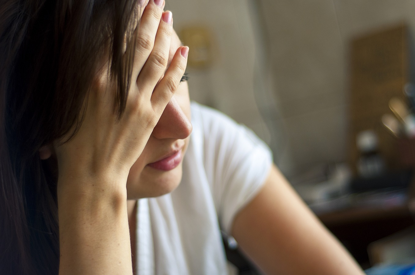 Woman feeling overwhelmed, holding head in hands